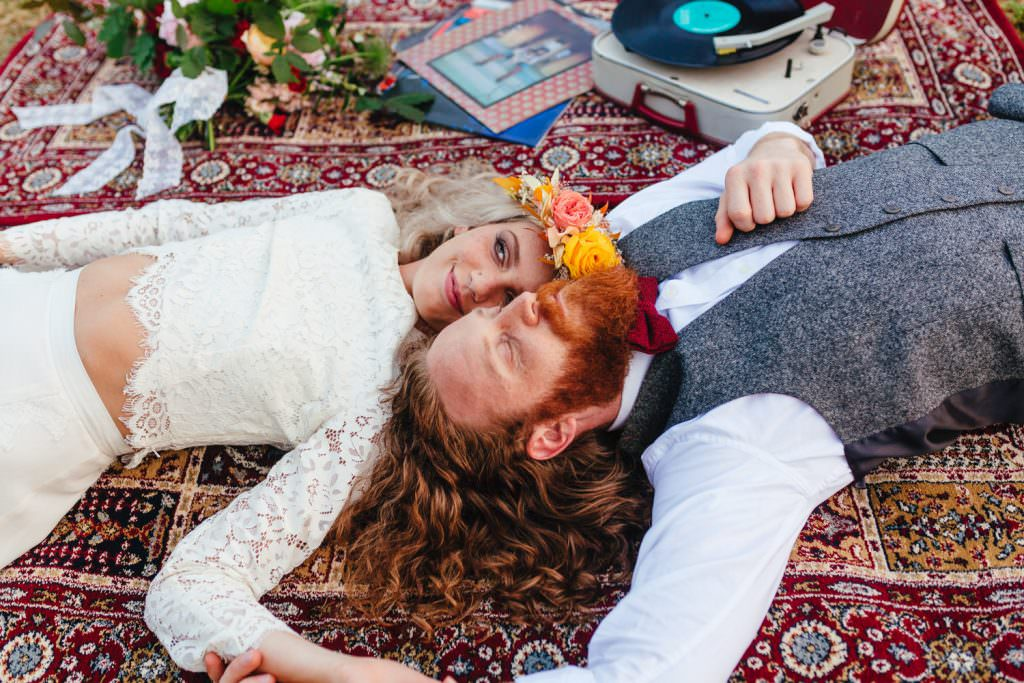 Bride wearing indie bride london two piece lying on persian rug during fun Sussex festival wedding photography.