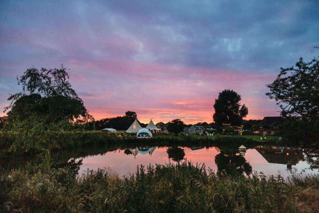 Amazing pink sky over tipi at Rye Island during fun Sussex festival wedding photography.