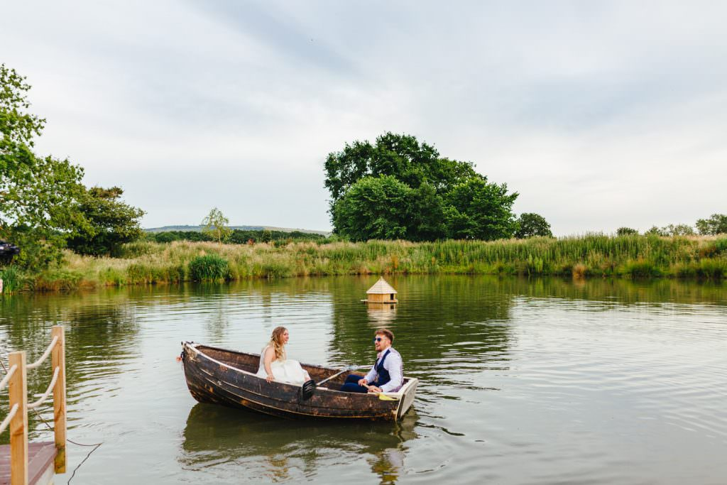 Bride and groom in a lake on rye island during fun Sussex festival wedding photography.