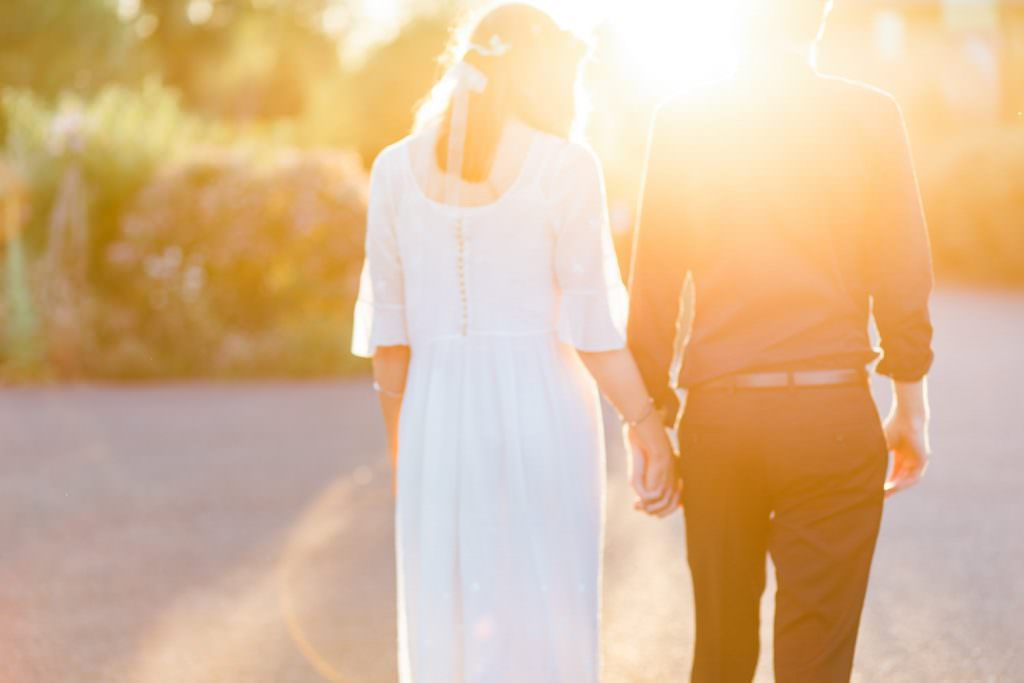 bride and groom walking in golden hour during fun Sussex festival wedding photography.