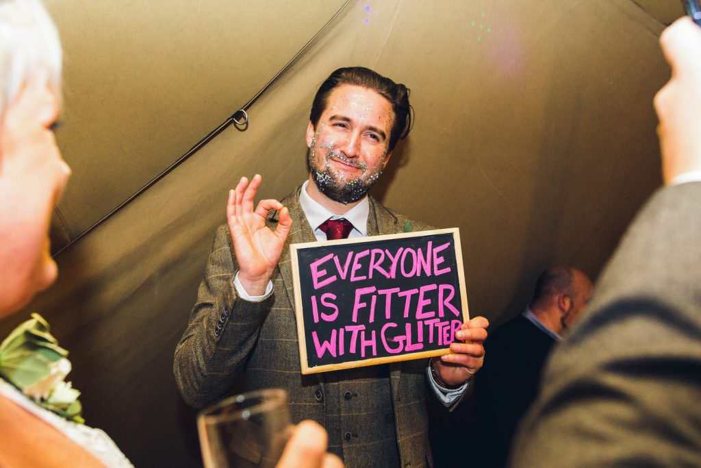 "During fun Sussex festival wedding photography guest with glitter in his beard holding a ""everyone is fitter with glitter"" sign."