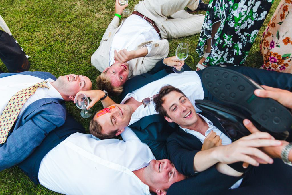 fun Sussex festival wedding photography. group of wedding guests on the floor having fun