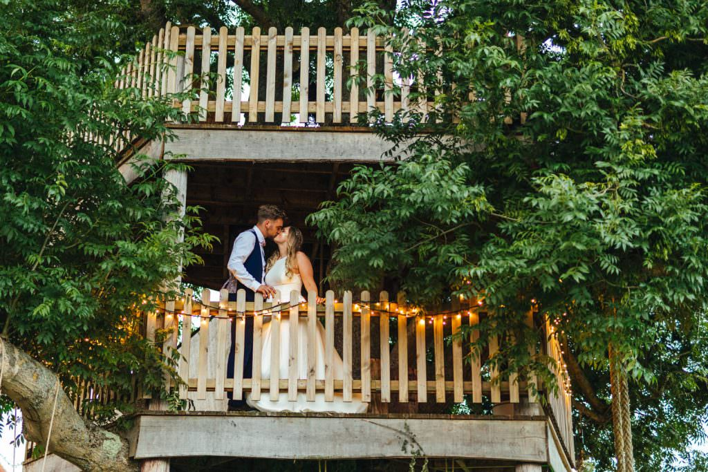 Bride and groom in treehouse during fun Sussex festival wedding photography.
