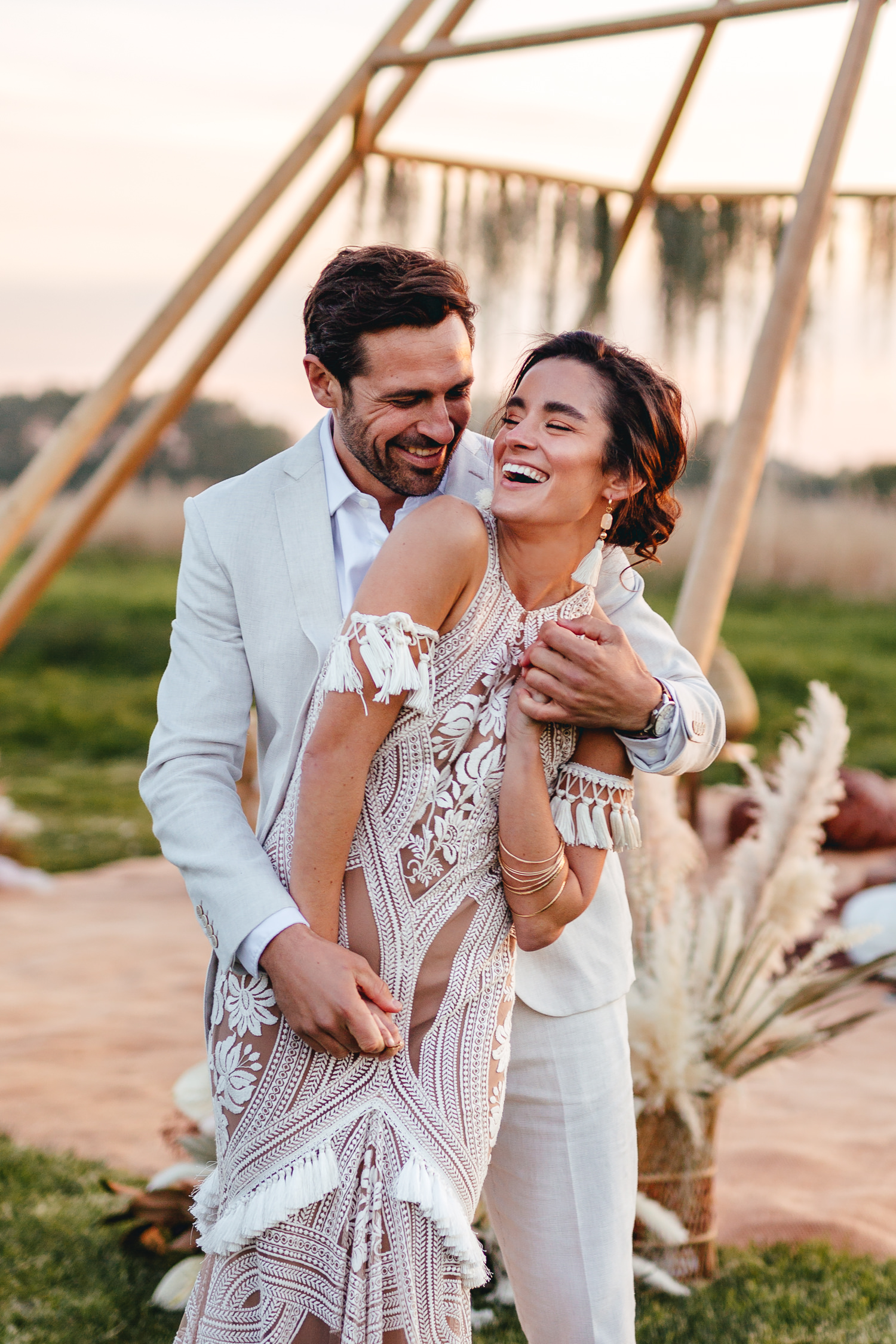 Relaxed boho wedding photography. Boho bride and bouquet of flowers with pampas grass. Bride wears Rue De Seine dress during Moroccan inspired festival wedding at Wilderness wedding venue in Kent