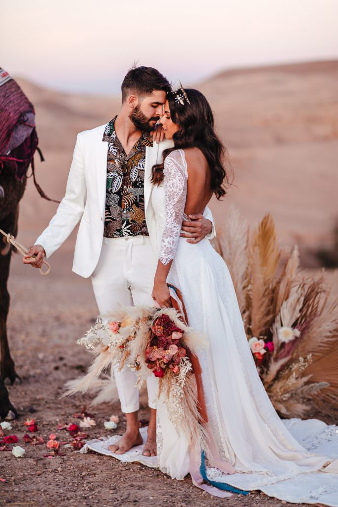 Bride and groom during Wedding Photography in Agafay Desert Morocco. Bride wears grace loves lace dress.