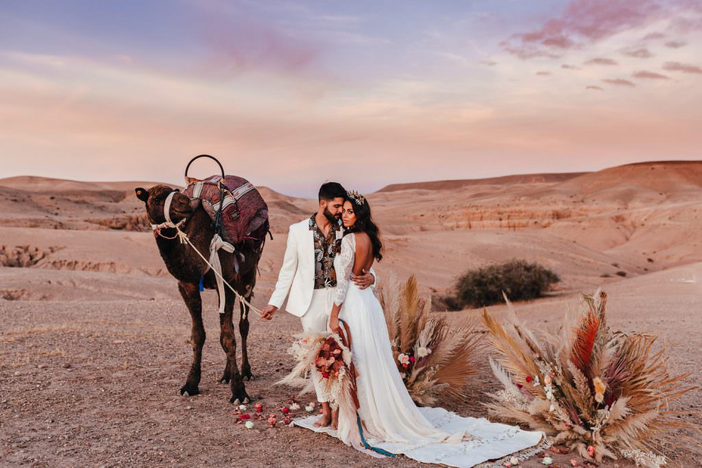 Bride and groom during Wedding Photography in Agafay Desert Morocco. Bride wears grace loves lace dress. Couple with Camel