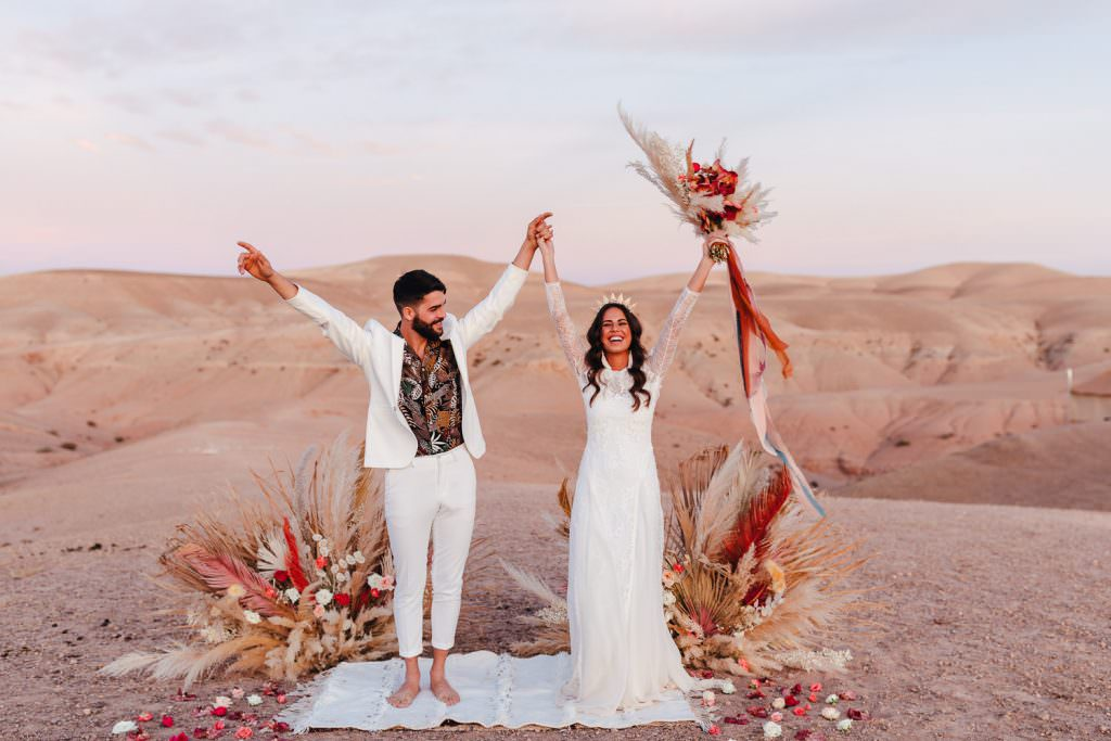 Bride and groom during Wedding Photography in Agafay Desert Morocco. Bride wears grace loves lace dress. Pampas Grass Florals
