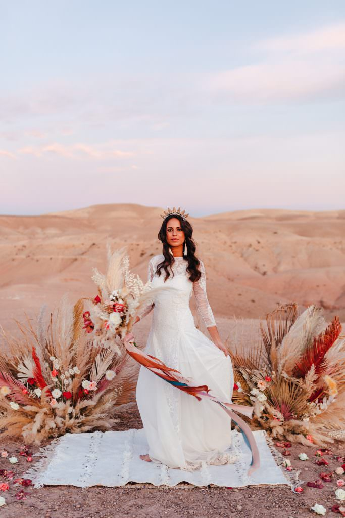 Bride during Wedding Photography in Agafay Desert Morocco. Bride wears grace loves lace dress. Pampas Grass Florals