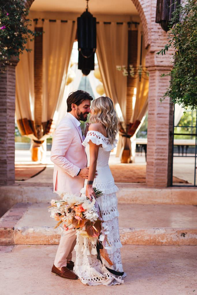 bride wears grace loves lace boho dress and hugs her groom at Beldi Country Club Wedding Morocco
