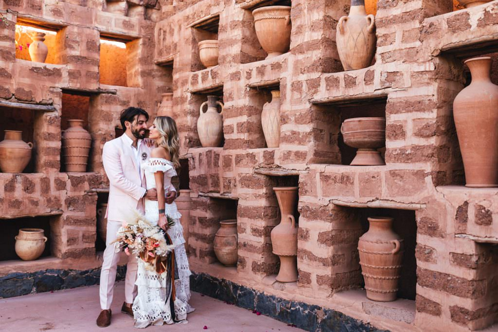 bride wears grace loves lace boho dress and poses with groom in front of Moroccan pots at Beldi Country Club Wedding Morocco
