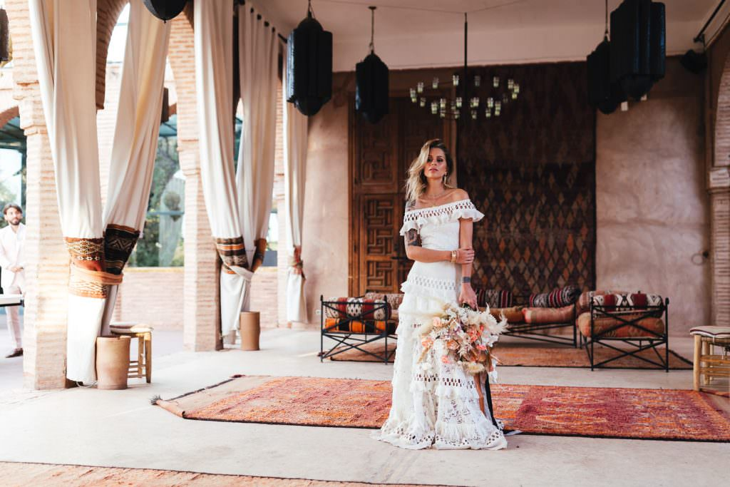 Bridal portrait in grace loves lace dress at Beldi Country Club Wedding Morocco. She stands with Persian Rugs and Boho Fashion