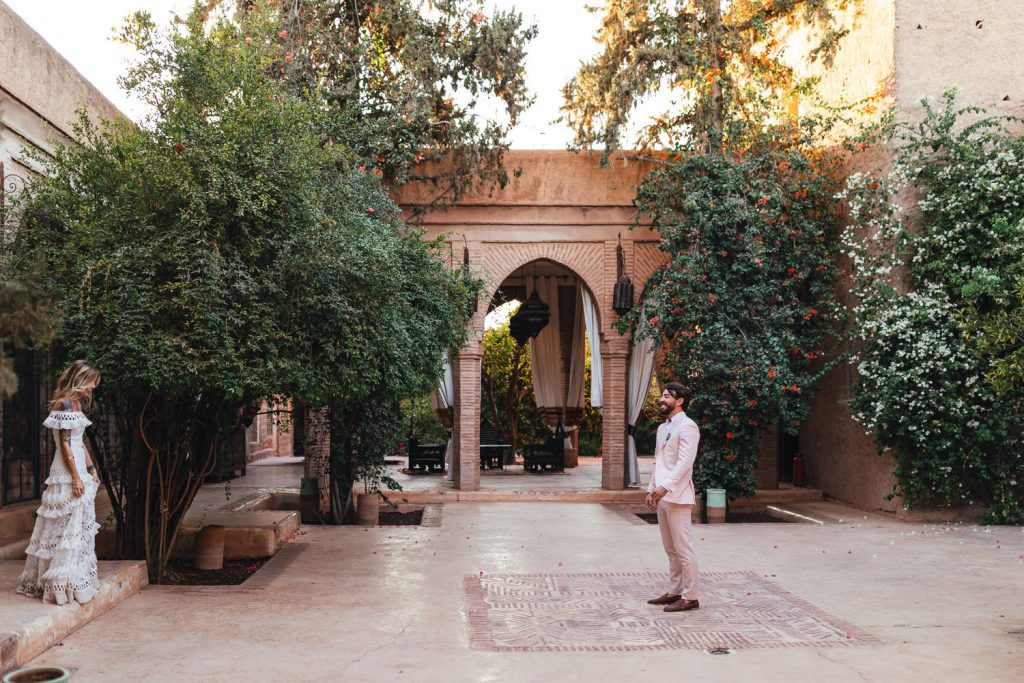 Groom waits to see her bride for the first time on their wedding day. First look at Bridal and groom natural couple photos in grace loves lace dress at Beldi Country Club Wedding Morocco. Persian Rugs and Boho Fashion