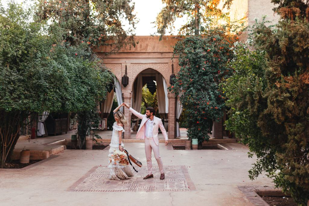 Bride and groom dance at Bridal and groom natural couple photos in grace loves lace dress at Beldi Country Club Wedding Morocco. Persian Rugs and Boho Fashion
