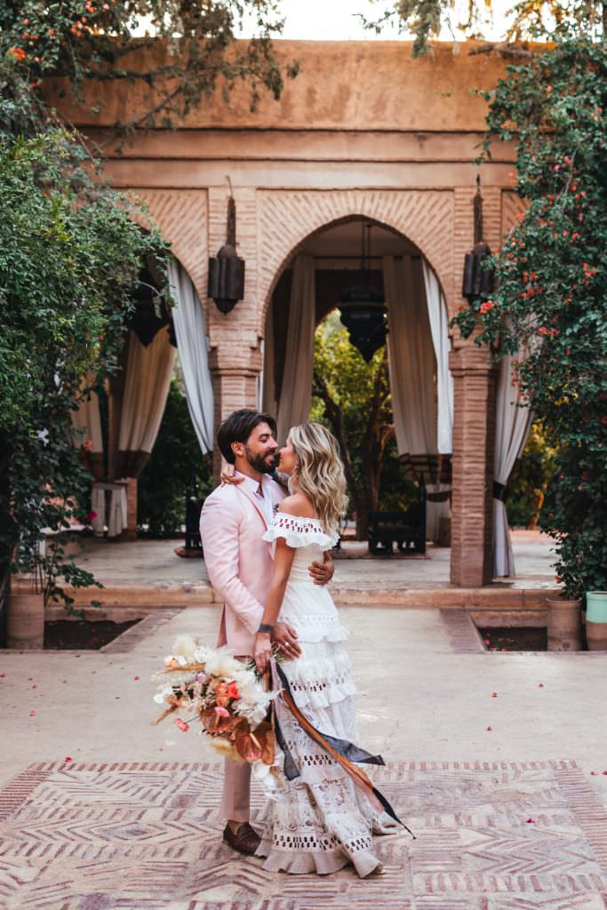 Bride and groom hug, natural couple photos in grace loves lace dress at Beldi Country Club Wedding Morocco. Persian Rugs and Boho Fashion