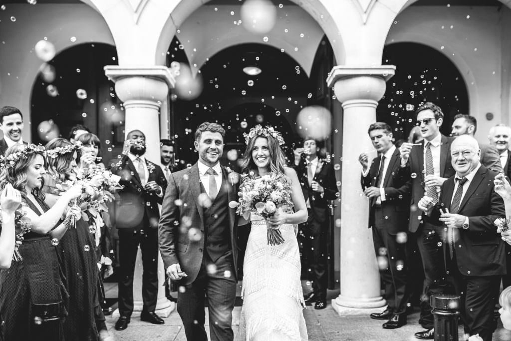 Bubble exit instead of confetti exit during during Brook Farm Festival Wedding Photography in Hertfordshire. Design by watters bohemian wedding dress