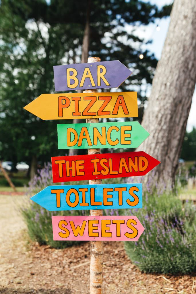 Colourful festival wedding sign during during Brook Farm Festival Wedding Photography in Hertfordshire.