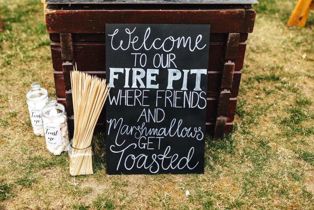 Welcome to our fire pit sign during during Brook Farm Festival Wedding Photography in Hertfordshire. Design by watters bohemian wedding dress