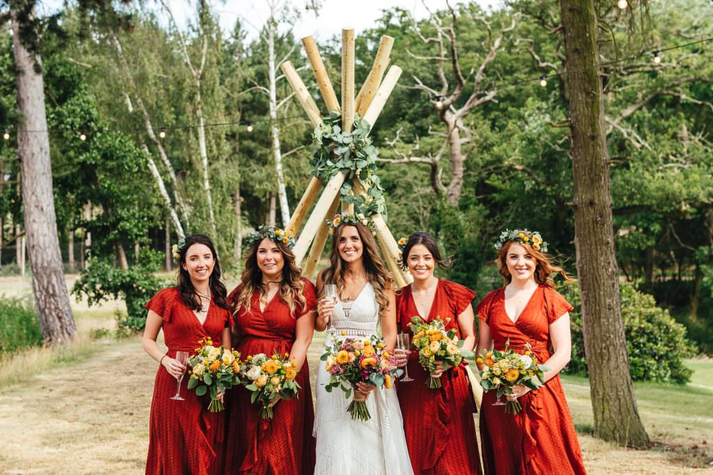 Boho Bride and bridesmaids during during Brook Farm Festival Wedding Photography in Hertfordshire. Design by watters bohemian wedding dress