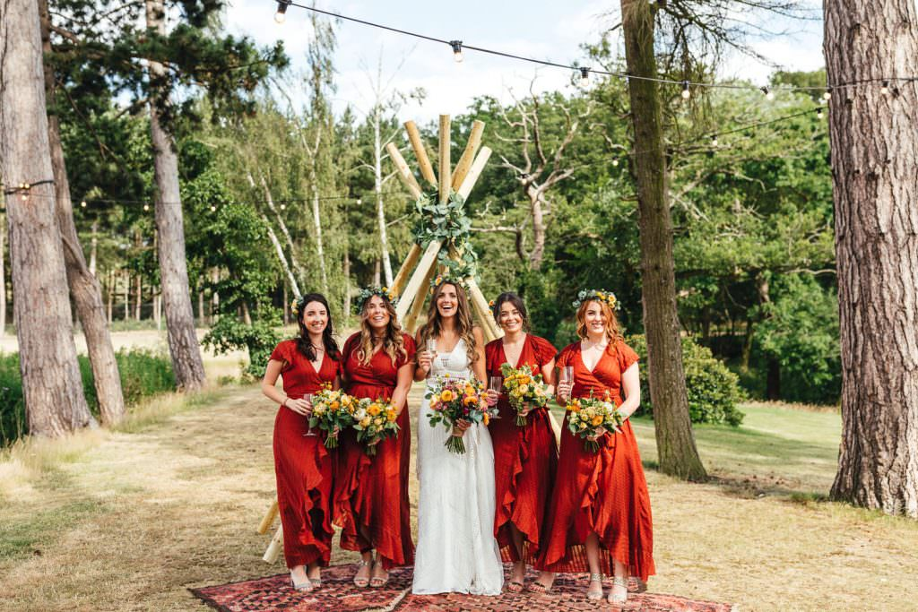 Bride and bridesmaids in rust bohemian dresses during during Brook Farm Festival Wedding Photography in Hertfordshire. Design by watters bohemian wedding dress