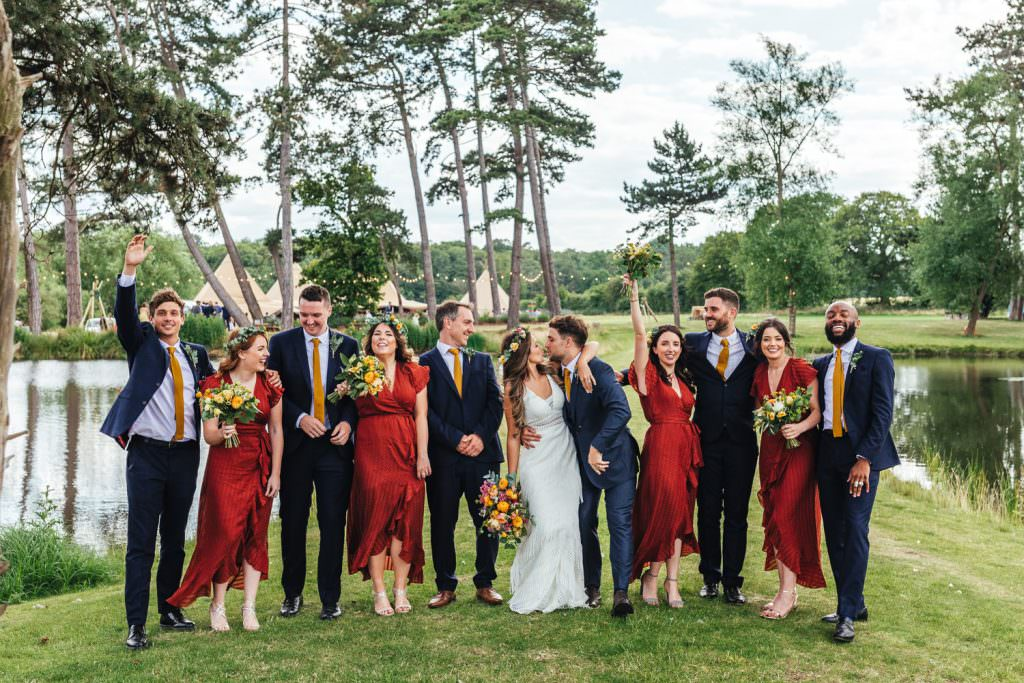 Bridesmaid and groomsmen natural wedding photography group shot during during during Brook Farm Festival Wedding Photography in Hertfordshire. Design by watters bohemian wedding dress