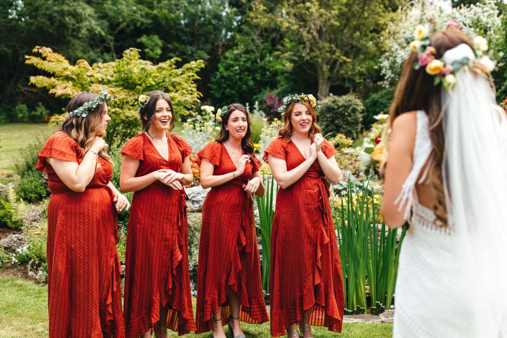 Bridesmaid reaction to bride in her dress during during during Brook Farm Festival Wedding Photography in Hertfordshire. Design by watters bohemian wedding dress