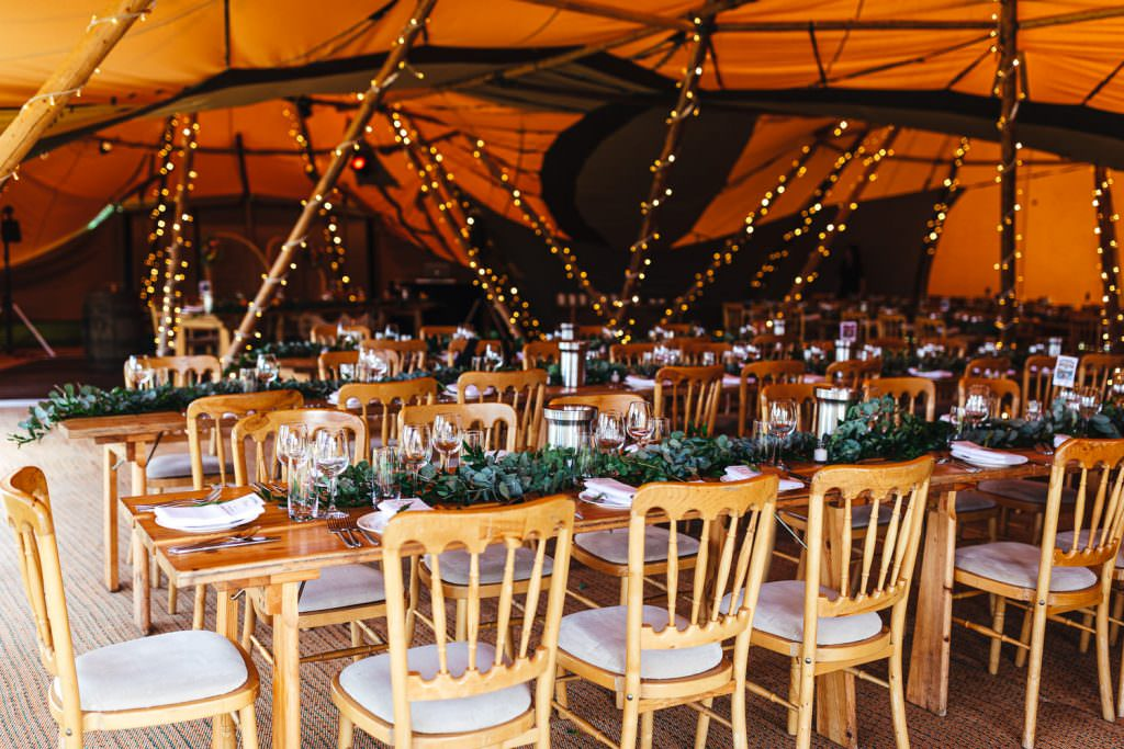 Boho tipi decor with greenery during during Brook Farm Festival Wedding Photography in Hertfordshire. Design by watters bohemian wedding dress