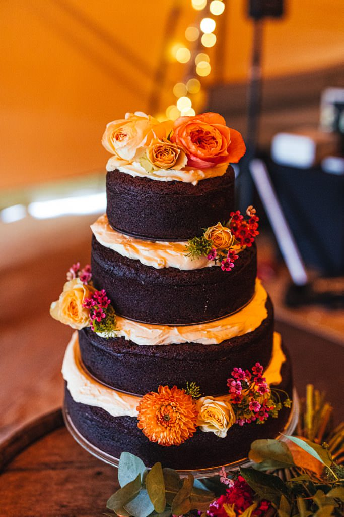 Boho dark chocolate wedding cake with orange florals for during Brook Farm Festival Wedding Photography in Hertfordshire
