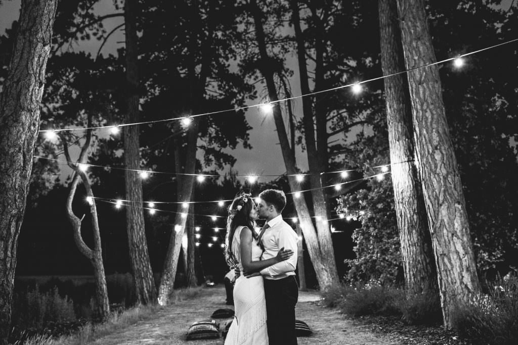 Couple under festoon lights during Brook Farm Festival Wedding Photography in Hertfordshire