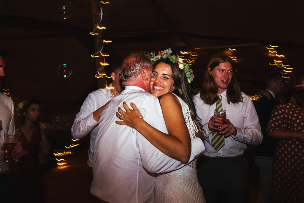 big hugs on the dancefloor during Brook Farm Festival Wedding Photography in Hertfordshire