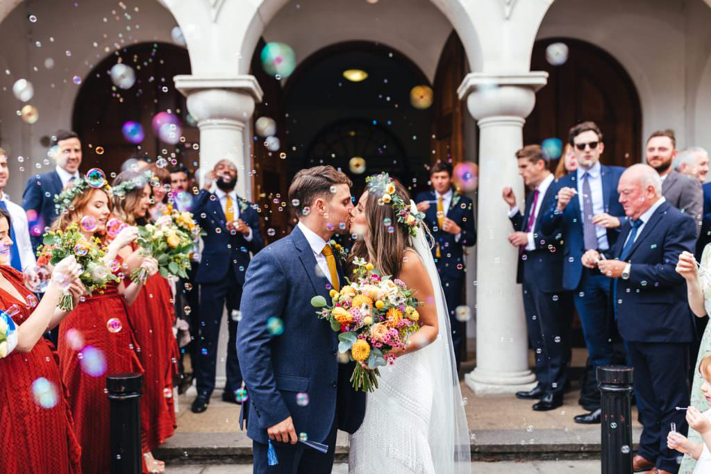 bubble exit instead of confetti during during Brook Farm Festival Wedding Photography in Hertfordshire. Design by watters bohemian wedding dress