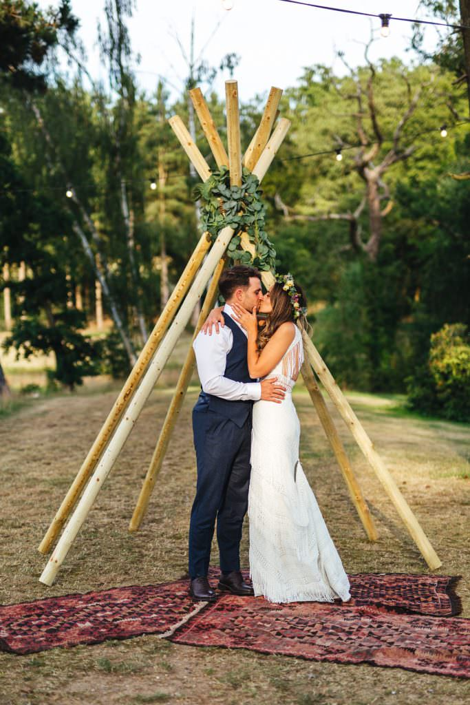Couple in boho chill out area during during Brook Farm Festival Wedding Photography in Hertfordshire. Design by watters bohemian wedding dress