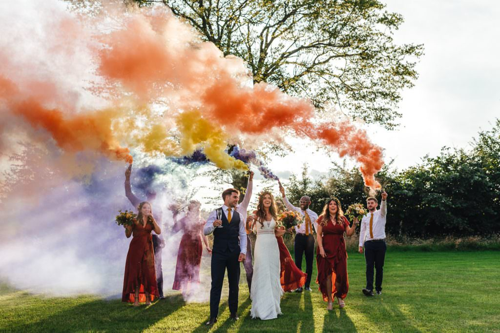 Colourful Smoke bombs during during Brook Farm Festival Wedding Photography in Hertfordshire. Design by watters bohemian wedding dress