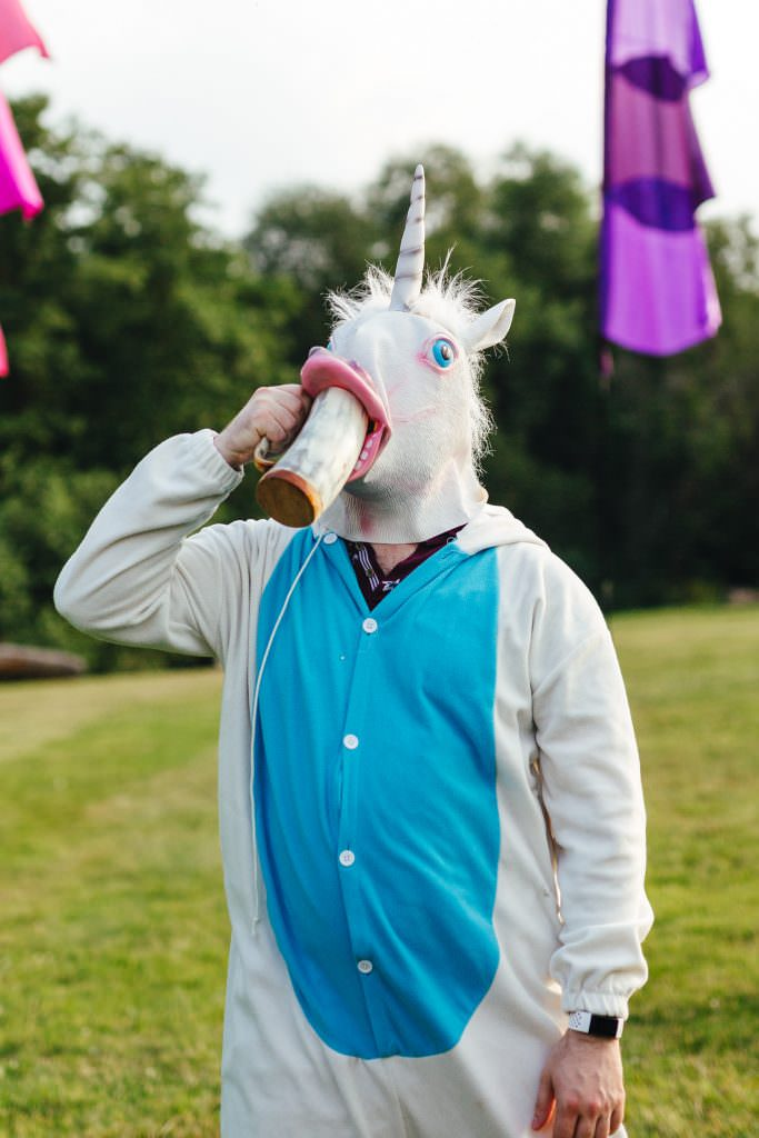 unicorn at a wedding drinking a beer. Smoke bombs in fields during Festival Frickley Lake Wedding | Sussex Wedding Photography