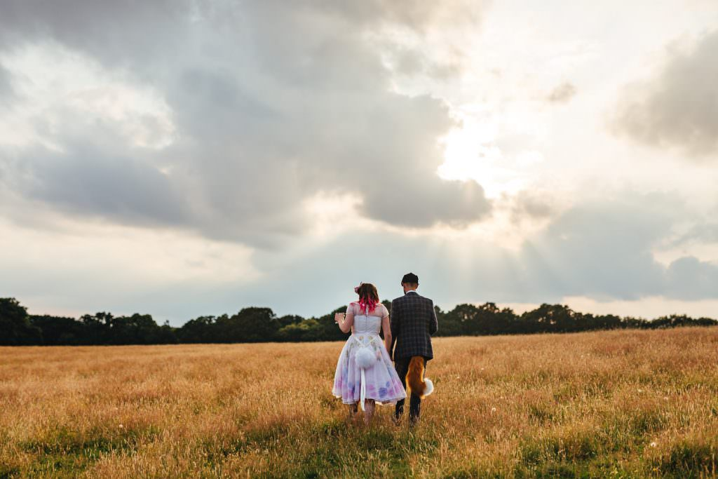 Bride and groom walking in a field at  Festival Frickley Lake Wedding | Sussex Wedding Photography