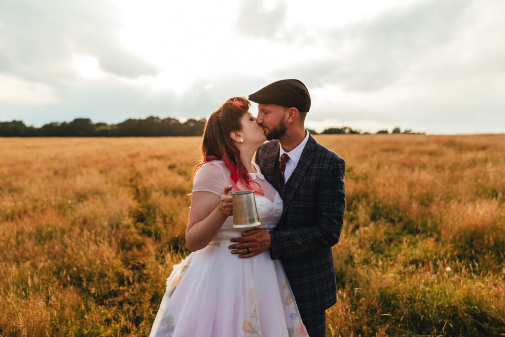 Bride and groom in field kissing at golden hour during Festival Frickley Lake Wedding | Sussex Wedding Photography