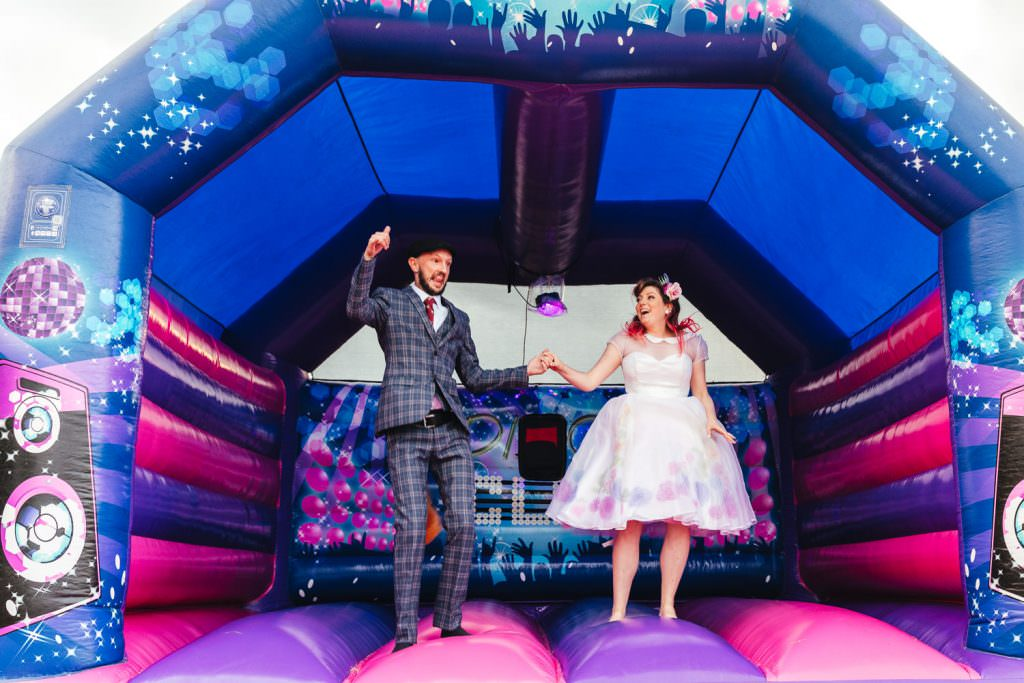 Fun with bride and groom on a bouncy castle during Festival Frickley Lake Wedding | Sussex Wedding Photography. Alternative wedding photographer
