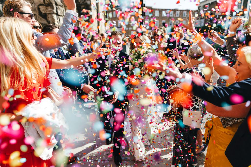 Bride and groom doing confetti exit, very colourful and full during a London Wedding at Battersea Power Station