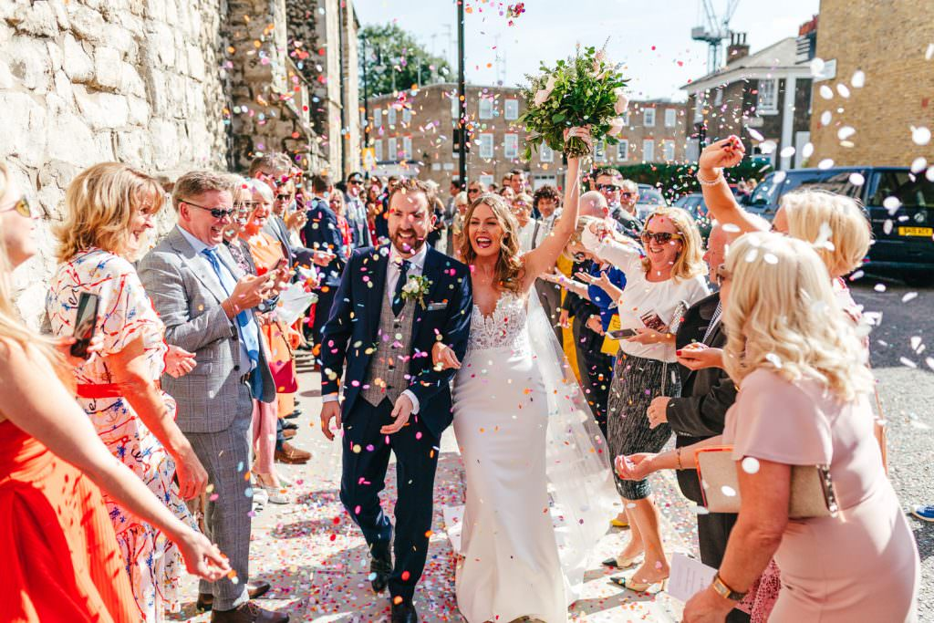 bride and groom colourful confetti exit during London Wedding at Battersea Power Station