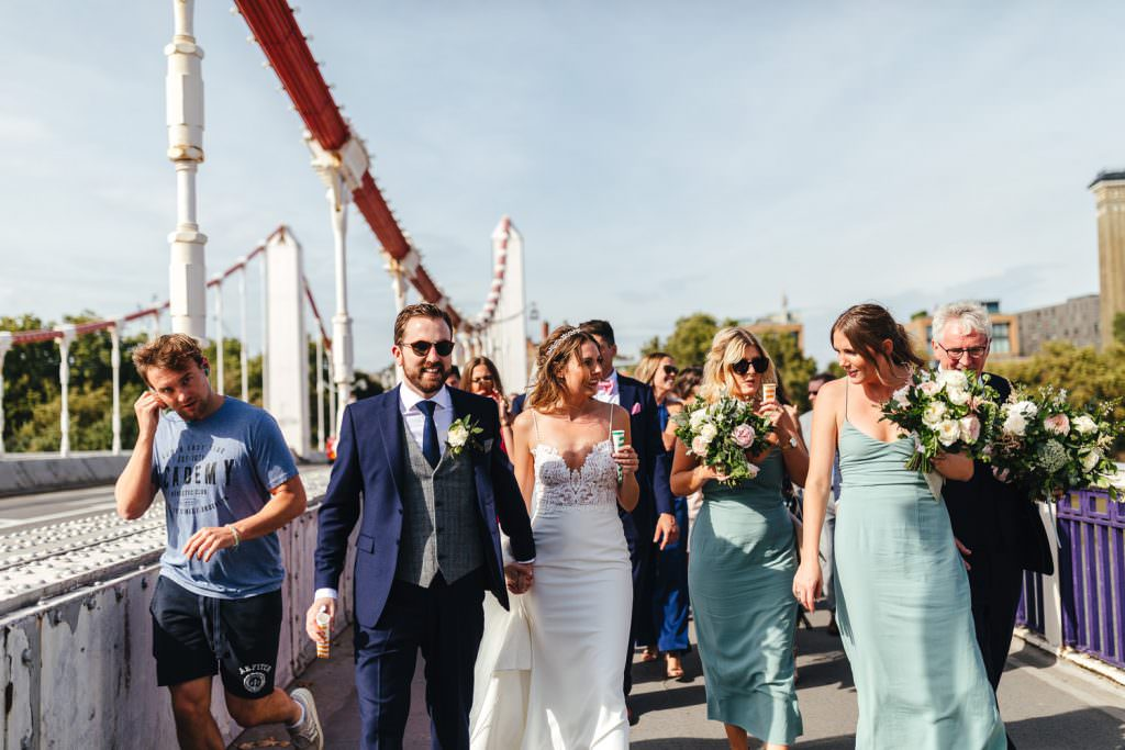 Bride and groom and wedding party walk over Chelsea Bridge at London Wedding at Battersea Power Station