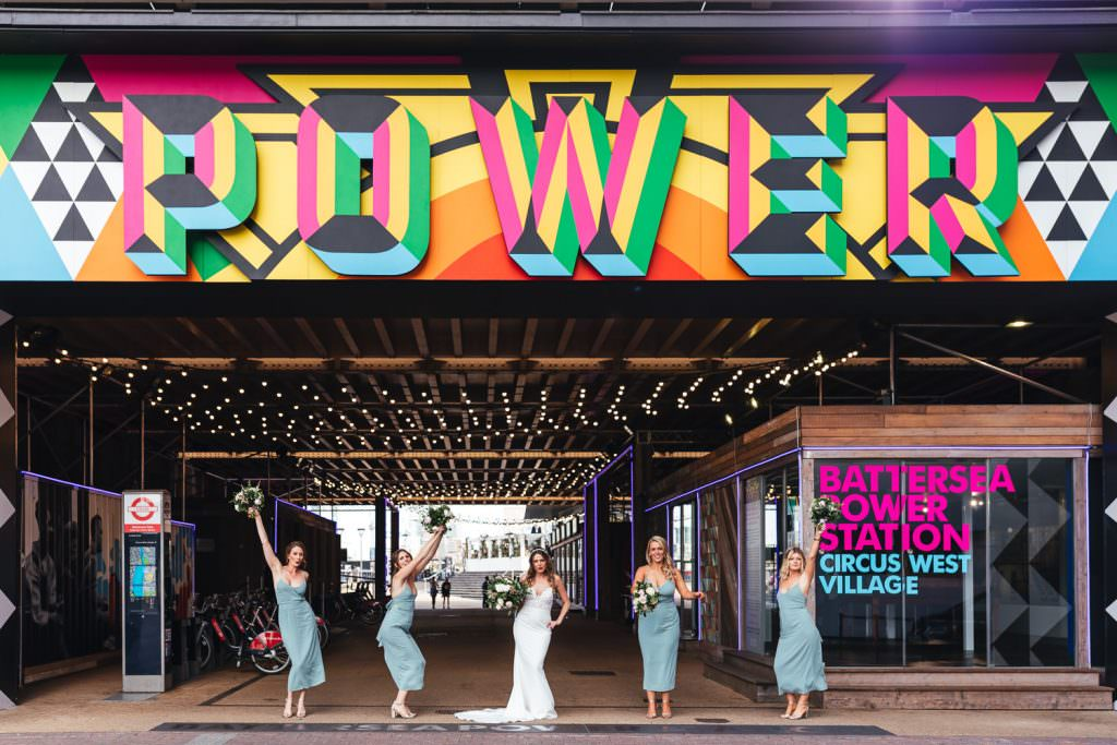 Bride and her bridesmaids under the power sign at No.29 power station west during London Wedding at Battersea Power Station