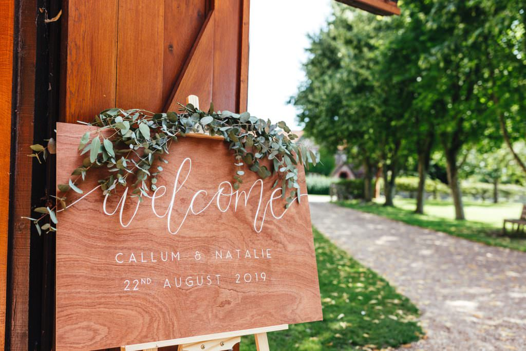 Wooden Welcome sign to wedding at Tithe Barn Petersfield Wedding