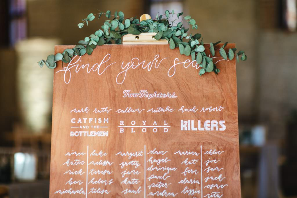 Wooden DIY seating plan inspired by couples favourite bands at Tithe Barn Petersfield Wedding