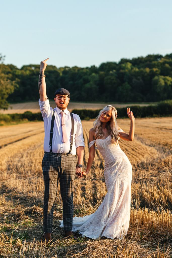 Fun alternative and quirky couple photographs in a field at Tithe Barn Petersfield Wedding. Bride in Watters Boho Bohemian Dress