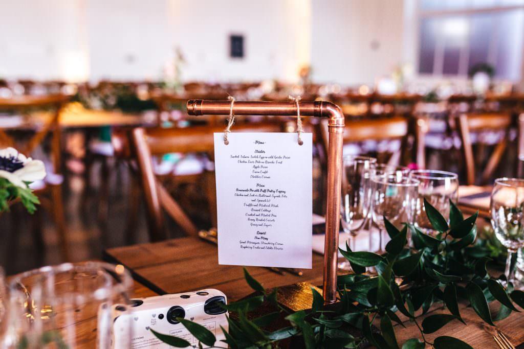 Cool copper menu at wedding. Industrial, modern wedding at Trinity Buoy Wharf. Urban Neon Wedding. Alternative wedding photography in London