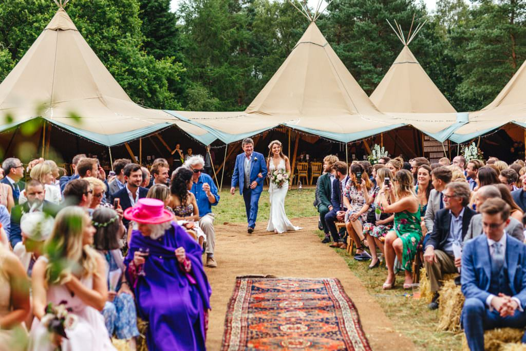 Bride and dad enter the aisle with beautiful world tents tipis in the background during Summer Festival Wedding Hampshire Photography