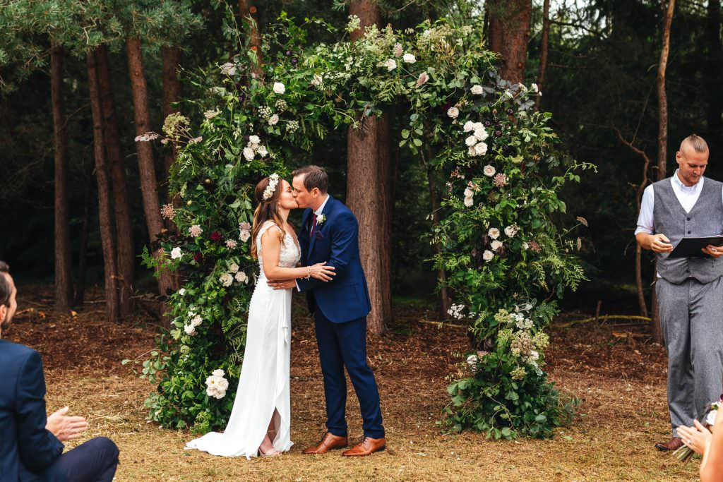 First kiss after getting married in front of a huge floral arch during Summer Festival Wedding Hampshire Photography