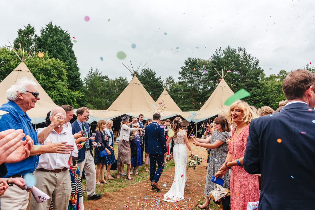 Confetti exit with beautiful world tents tipis in the background during Summer Festival Wedding Hampshire Photography
