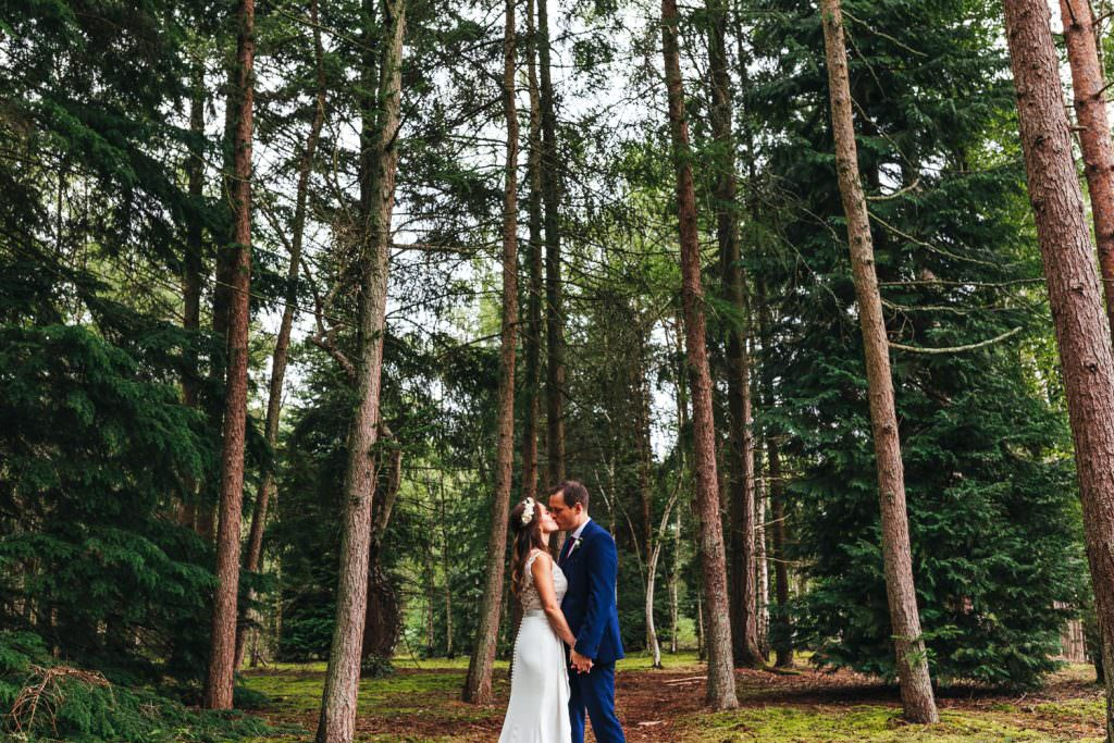 Bride and groom kissing in a woods at Summer Festival Wedding Hampshire Photography