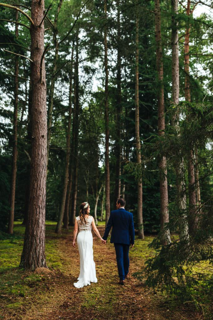 Woodland wedding photography at Summer Festival Wedding Hampshire Photography. Bride and groom walking in woodland. Natural and relaxed couple portraits