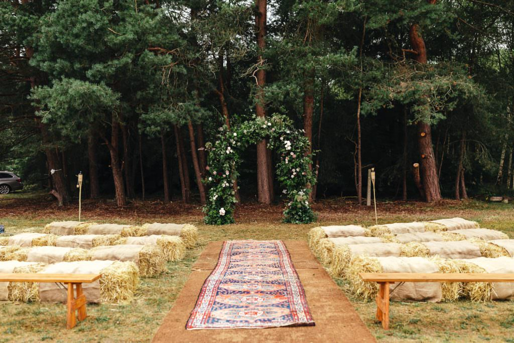 Summer Festival Wedding Hampshire Photography ceremony set up with persian rugs and floral arch